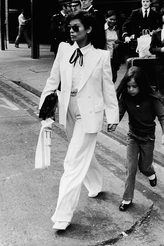 Bianca-Jagger-wears-double-breasted-white-suit-as-she-&-daughter-Jade-walk-across-street-in-London,-May-4,-1979