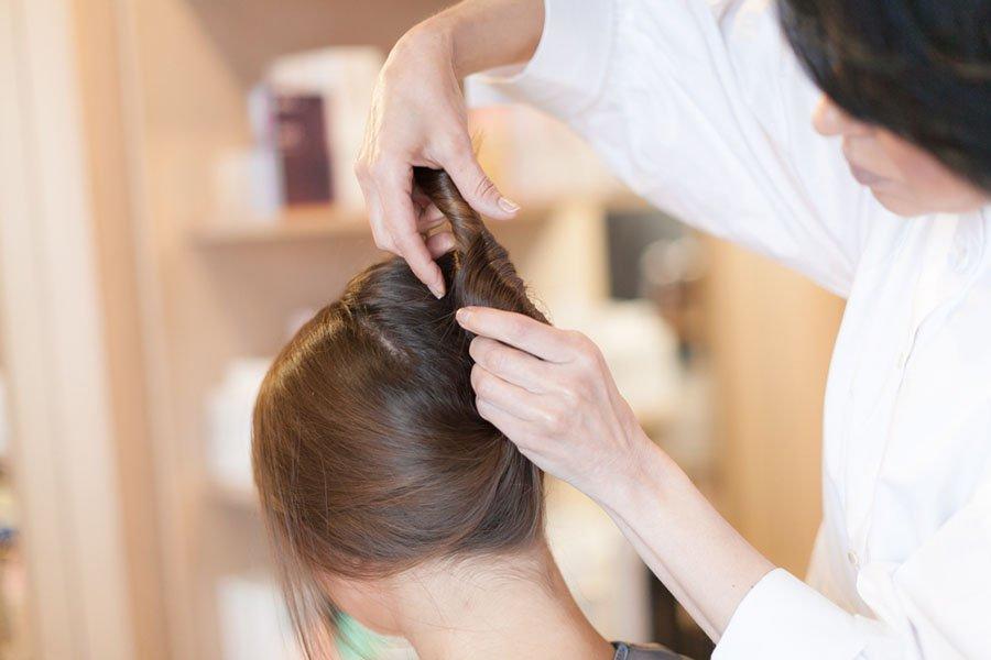 """Оставьте свободные пряди у лица. Из остальных волос сделайте смотрящий вниз жгут (запомните, в какую сторону крутите – вправо или влево) и направьте его вверх, как на фото. Длинные волосы придется """"сложить"""" вдвое или даже втрое. То есть снова направить вниз-вверх."""